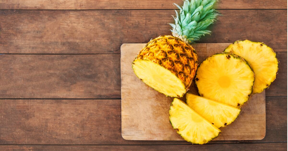 Pineapple cut up on a wooden chopping board