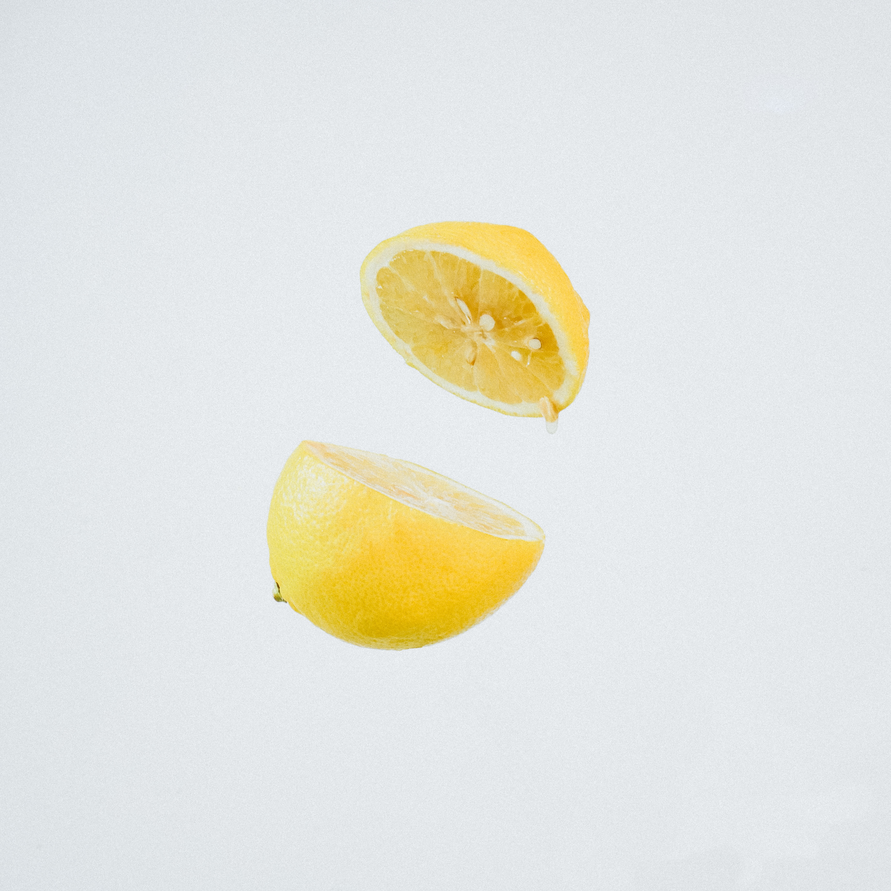 A lemon cut in half and suspended mid-air