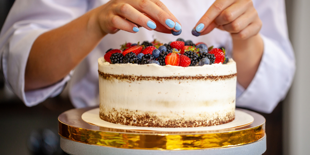 Hands seen decorating a cake with fruit