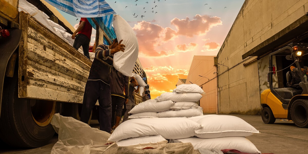 Workers unload bagges sugar from a truck against a sunset